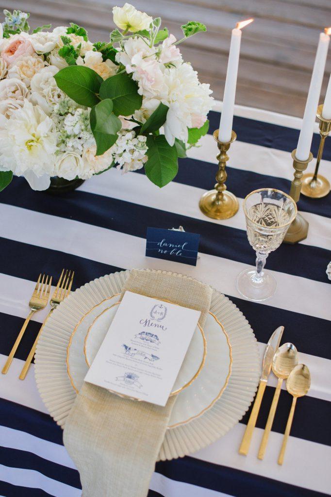 In questa foto una mise en place a tema navy con piatto e posate dorate e tovagliato a righe bianche e blu