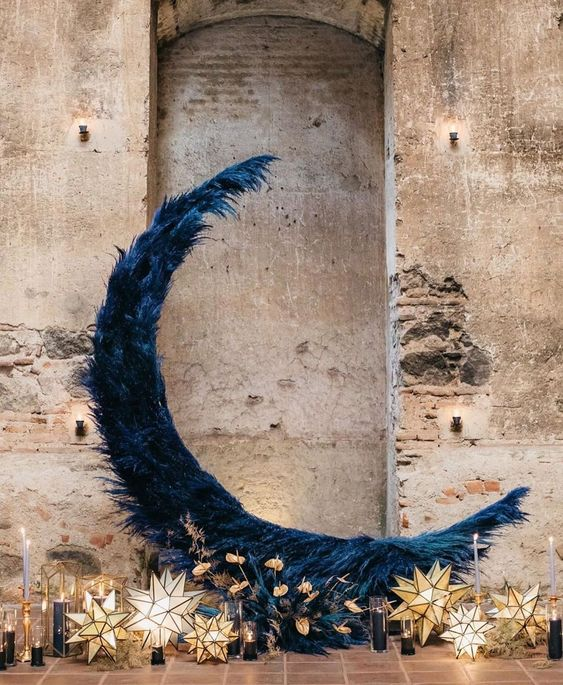 In questa foto una luna gigante di piume blu perfetta come decorazione per un matrimonio a tema blu