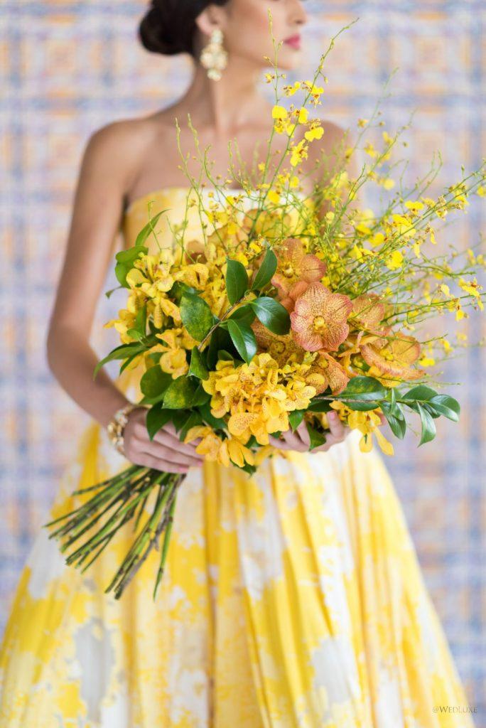 In questa foto una modella vestita di giallo tiene tra le mani un bouquet da sposa a braccio con fiori gialli