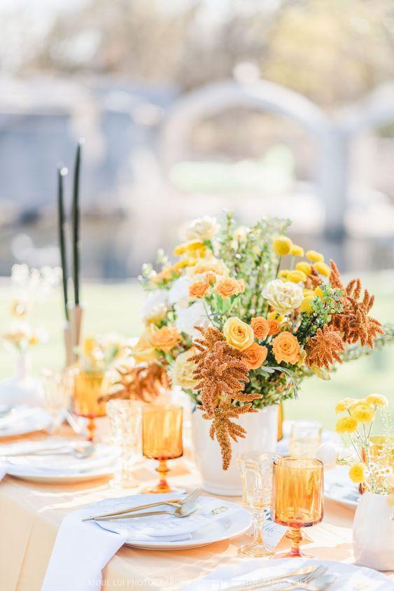 In questa foto una mise en place per un matrimonio a tema giallo e arancio, perfetta per nozze primaverili. Come centrotavola è presente un vaso di fiori di campo e tovagliato e bicchieri sono in pendant.