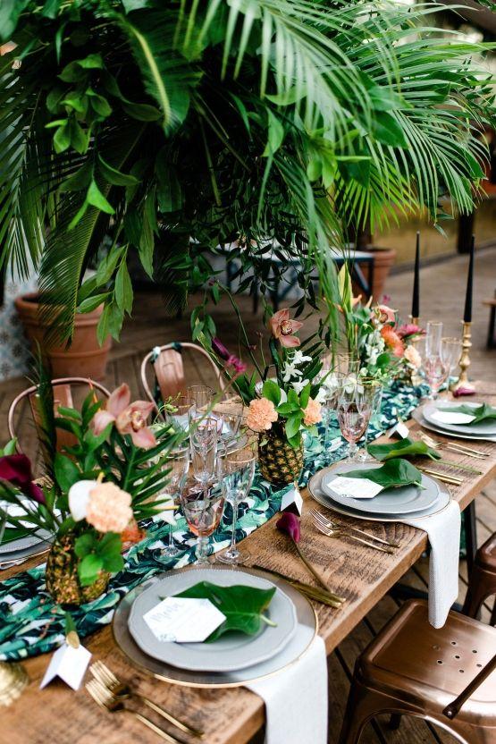 In questa foto un tavolo matrimonio imperiale in legno visto dall'alto in stile jungle con con palme, orchidee e ananas come centrotavola. I piatti sono bianchi, i sottopiatti trasparenti con bordi colore oro e ci sono foglie larghe come segnaposto
