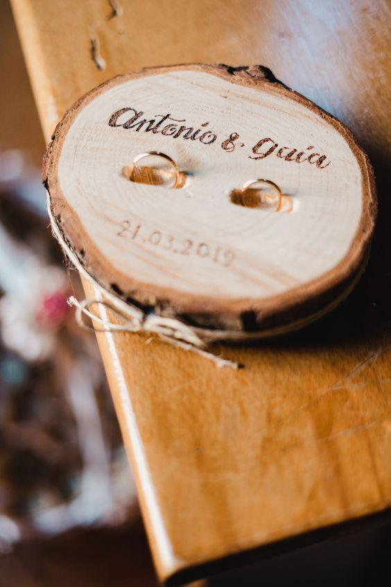 In questa foto un portafedi realizzato con un pezzetto rotondo di tronco d'albero con i nomi degli sposi e la data delle loro nozze