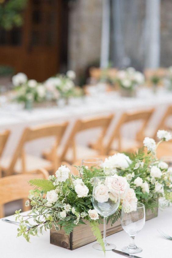 In questa foto un centrotavola con rose e boccioli bianchi e felci contenute in un box di legno chiaro per un ricevimento di nozze all'aperto con sede in legno e tavoli imperiali. Tovaglie bianche completano l'allestimento