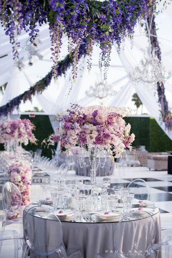 In questa foto un allestimento di nozze con tovagliato color lavanda e centrotavola in coordinato con cristalli e fiori bianco. Il ricevimento si svolge sotto un tendone di stoffa trasparente con archi di glicine e lampadari in cristallo