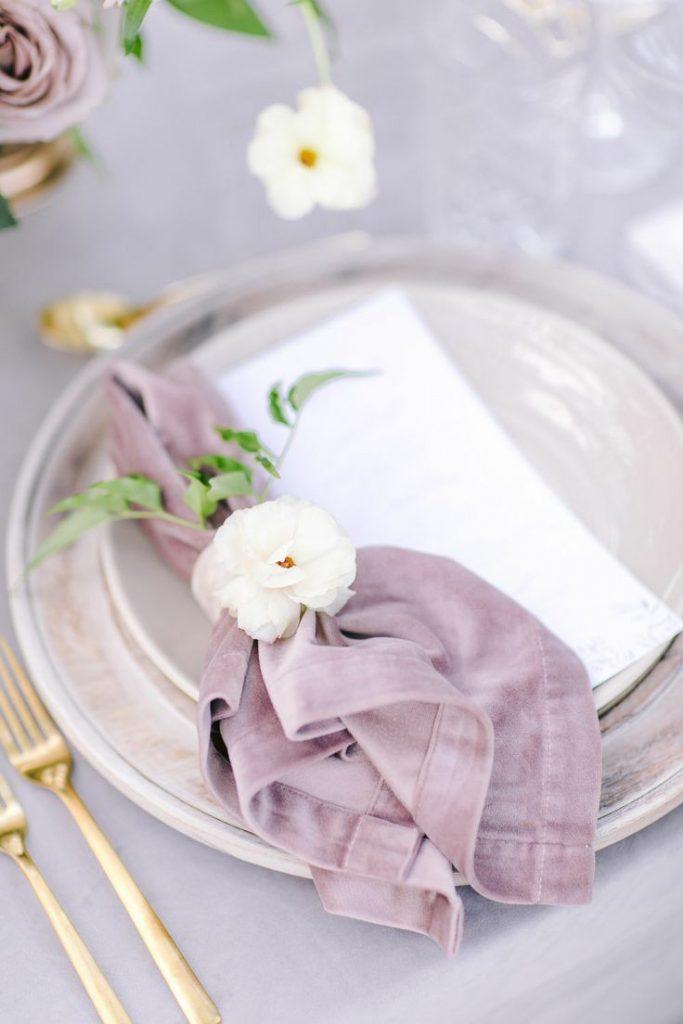 In questa foto un portatovagliolo lavanda e tovagliato in coordinato con un fiore bianco e posate oro
