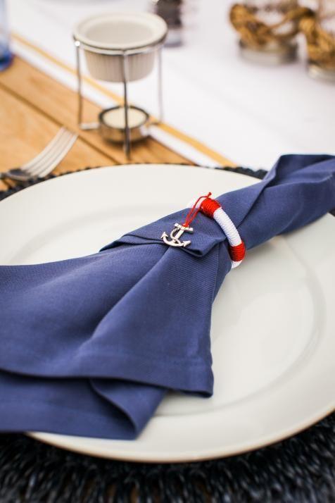 In questa foto un tovagliolo blu navy con fermatovagliolo rosso e bianco a forma di salvagente e un ciondolo ad ancora in metallo