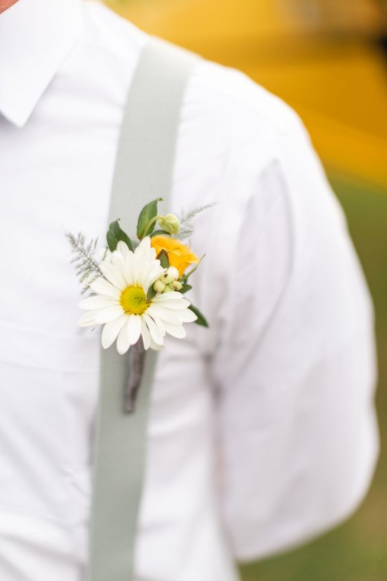 In questa foto la bottoniera con una margherita bianca dello sposo attaccata alle bretelle