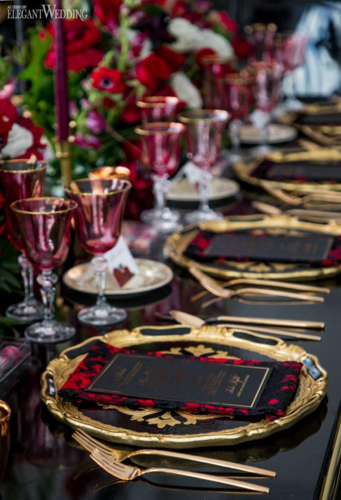 In questa foto una mise en place per un matrimonio vista in diagonale su un tavolo nero lucido, piatti e posate nel colore oro e bicchieri di cristallo magenta
