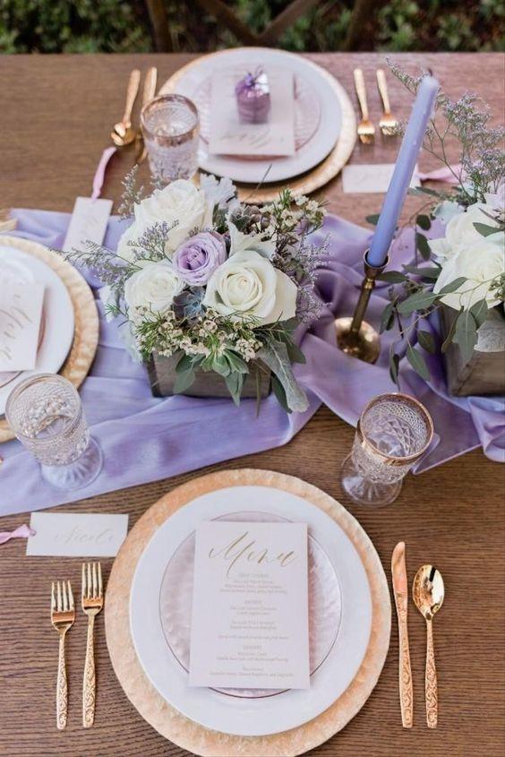 In questa foto una mise en place boho chic e romantica con runner lilla, centrotavola di rose bianche, piatti e posate in oro