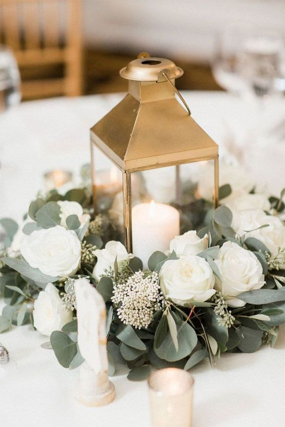 In questa foto un centrotavola per un matrimonio con lanterna di colore ore, rose e peonie bianche, alloro e candele