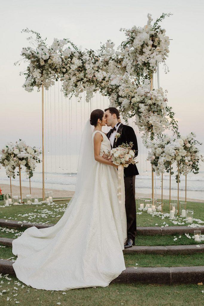In questa foto due sposi che si baciano dopo la celebrazione del loro matrimonio all'aperto sul mare