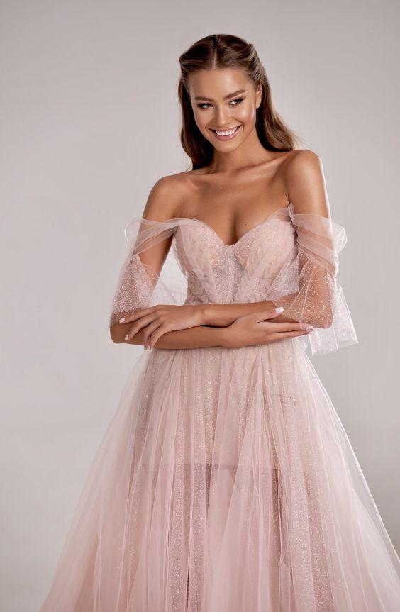In questa una modella indossa un abito da sposa rosa di Milla by Lorenzo Rossi