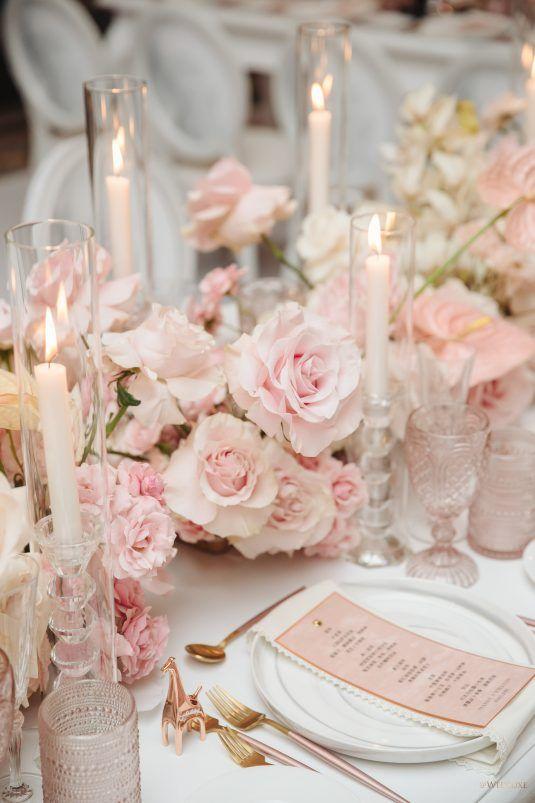 In questa foto una mise en place di un matrimonio in rosa con candele e segnaposto in coordinato