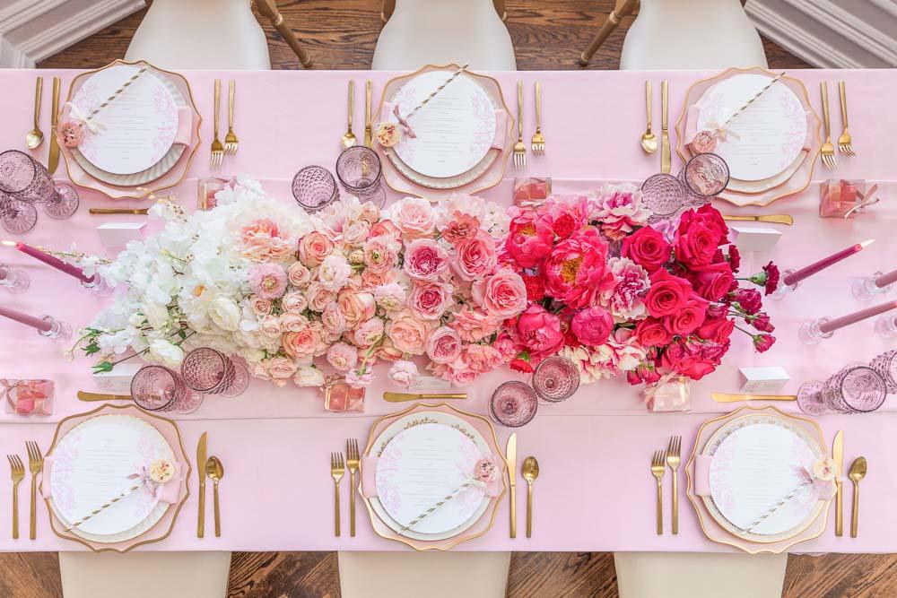 In questa foto un runner floreale visto dall'alto utilizzato come centrotavola per un matrimonio. I fiori utilizzati sono disposti in gradazione di colore dal bianco al rosa al fuxia