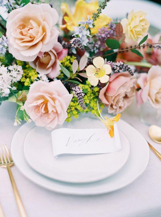In questa foto una mise en place elegante con tovagliato e piatti bianchi, posate oro e centrotavola di rose color pesca e fiori di campo
