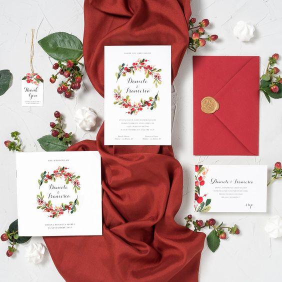 In questa foto partecipazioni di un matrimonio a tema rosso con runner in stoffa e vischio perfette per nozze natalizie