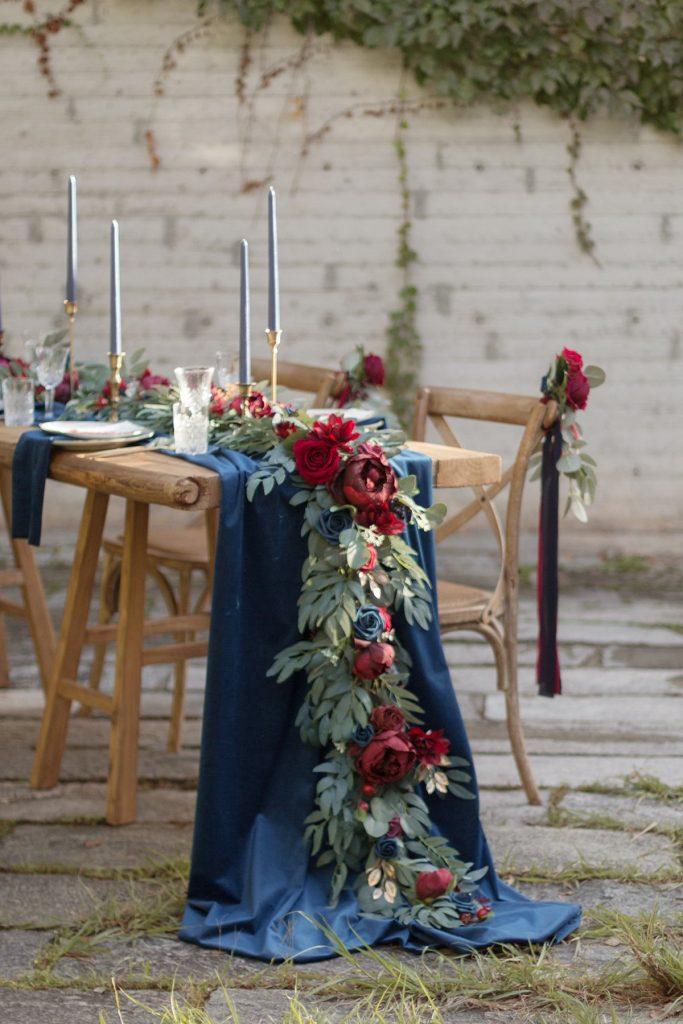 In questa foto l'allestimento di un tavolo matrimonio in legno nudo con runner di stoffa blu e runnere di foglie e grandi fiori blu e rossi