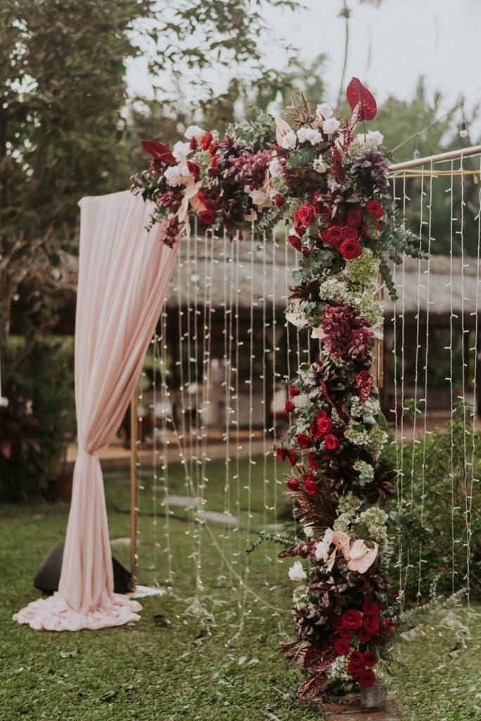 In questa foto un arco per un rito nuziale su un prato di fiori rossi, bianchi, verdi e rosa con tendaggi rosa confetto e e catenelle di cristalli