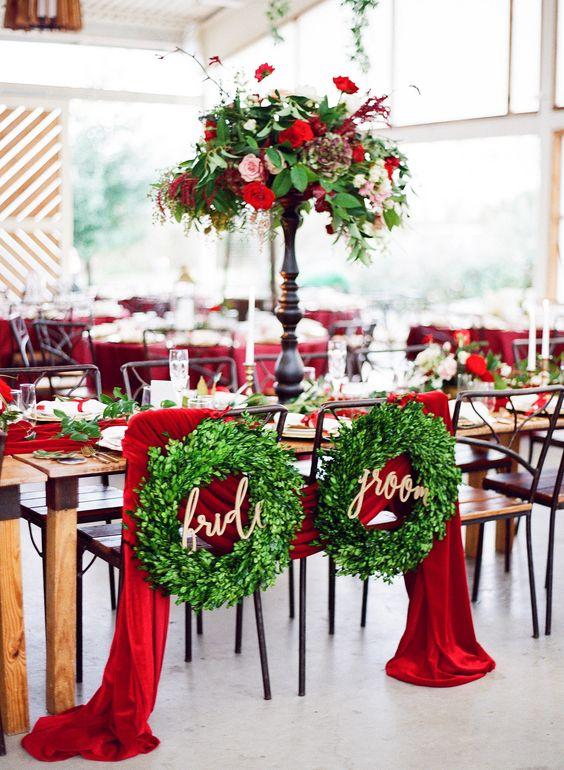 In questa foto il tavolo degli sposi con ghirlande verdi e tovagliato e tendaggi rossi