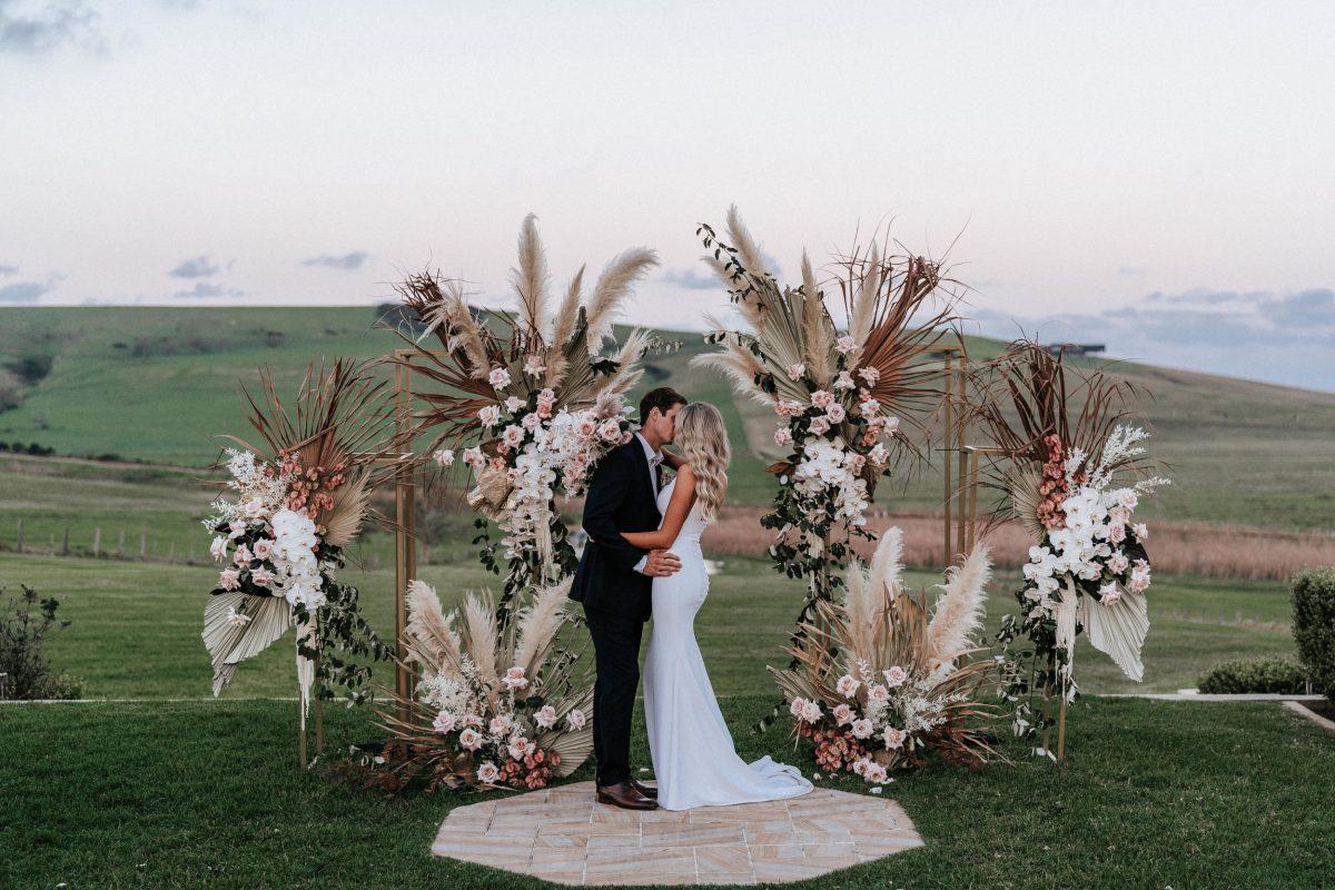 In questa foto due sposi che si baciano dopo la celebrazione del loro matrimonio in stile boho chic. Alle spalle, al posto dell'altare, un arco simbolico con pampas e rose