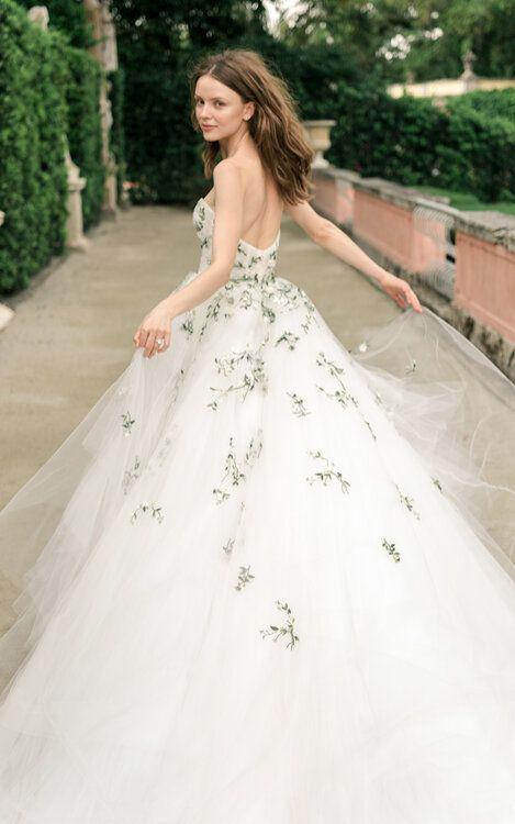 In questa foto una modella ripresa di spalle mentre corre, indossa un abito da sposa Monique Lhuillier con ramage floreali verdi