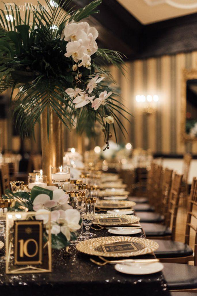 In questa foto un tavolo matrimonio imperiale nei colori del nero, dell'oro e del bianco. Vasi alti di colore oro con orchidee bianche e palmette sono usati come centrotavola insieme a delle candele basse