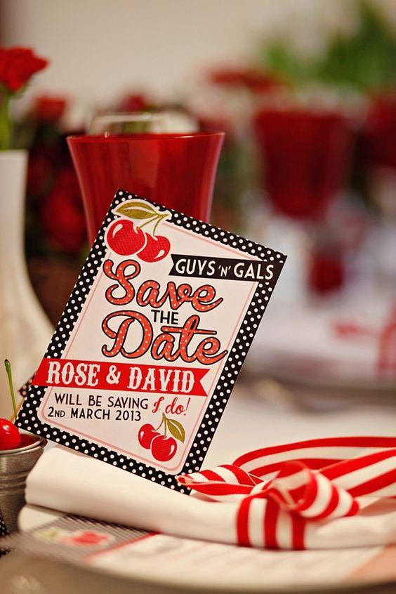 In questa foto una partecipazione di nozze a tema anni 50 a pois bianchi e neri con testi in rosso e decorazioni di ciliegine. La partecipazione è poggiata su un tovagliolo bianco