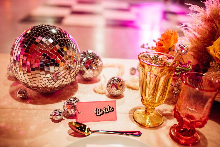 In questa foto il tavolo degli sposi con una palla stroboscopica colore argento, la targhetta rosa della sposa e bicchieri colorati. Un allestimento ideal per un matrimonio a tema anni 80