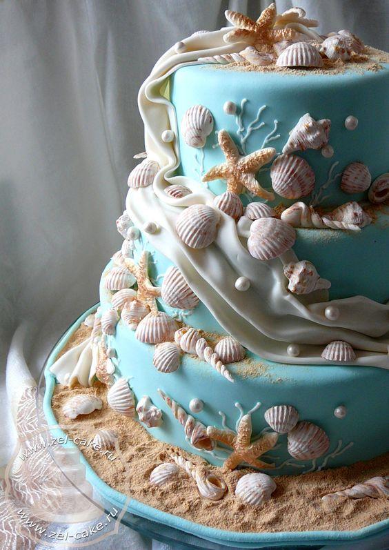 In questa foto una torta nuziale a tre piani con pasta di zucchero nel colore Tiffany decorata con tante conchiglie e stelle marine