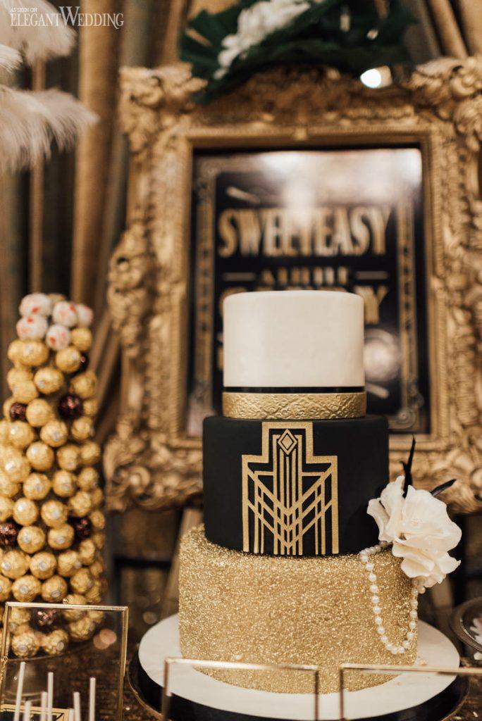 In questa foto uno sweet table, un angolo dolce, per un matrimonio anni 20 con una torre di cioccolatini e, in primo piano, una torta nuziale a tre piani nei colori oro, avorio e nero. Al centro è presente una decorazione geometrica mentre, al lato sinistro, perle e una rosa bianca