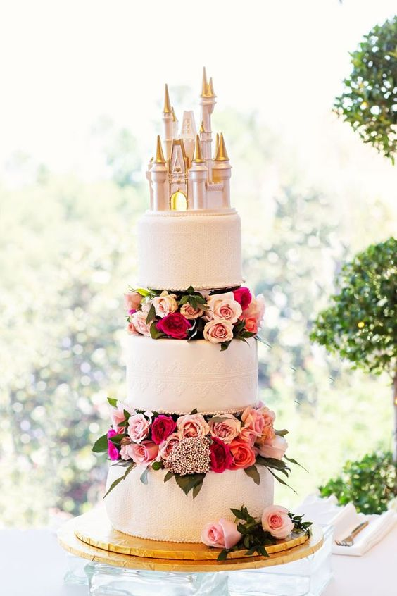 In questa foto una torta di matrimonio con un castello come cake topper