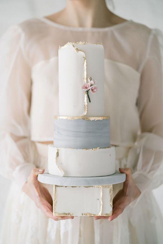 In questa foto una sposa tiene in mano una torta geometrica nei toni del bianco, grigio e oro