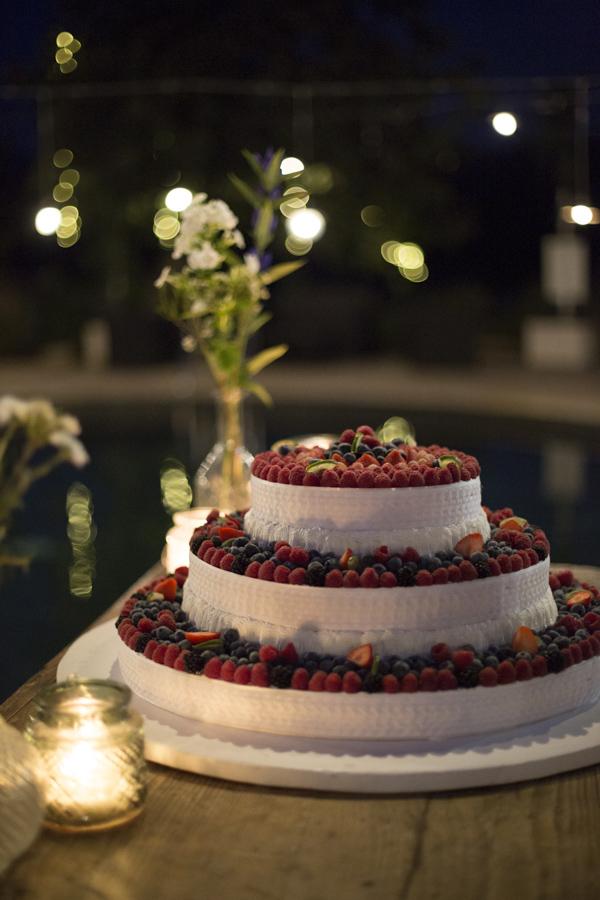 In questa foto una torta matrimoniale a tre piani a cappelliera, con panna e frutti di bosco