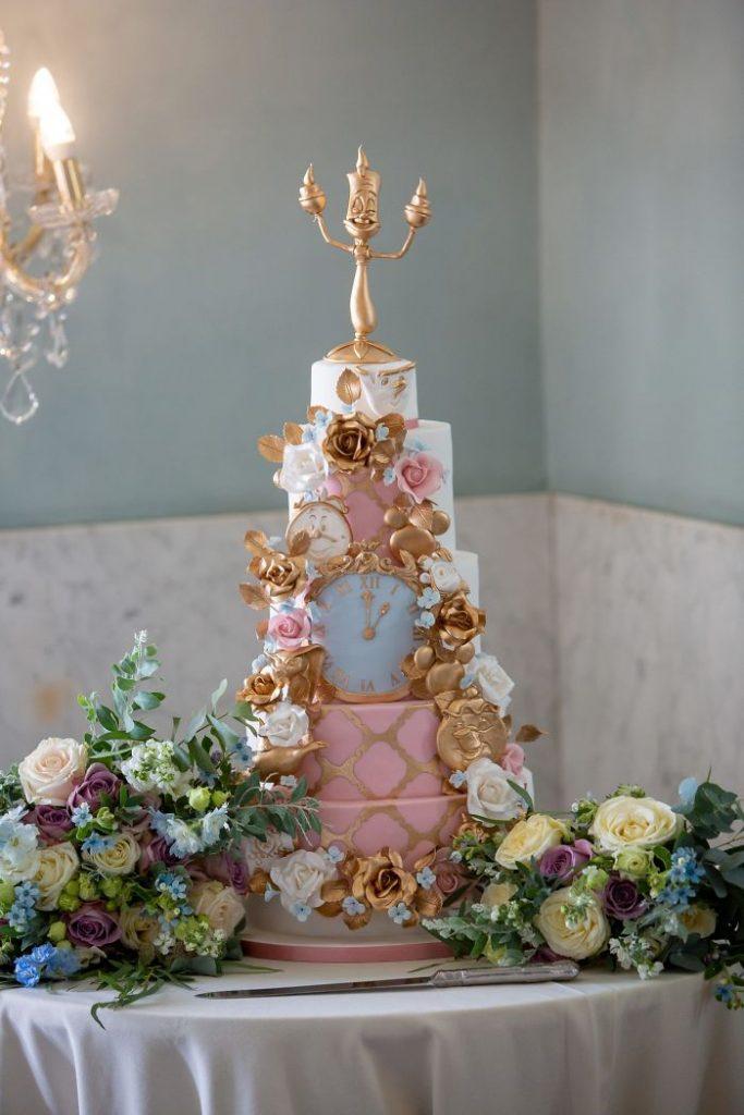 In questa foto una torta nuziale rosa, bianca e oro, ispirata a La Bella e al Bestia. Come cake topper il personaggio di Lumiere, il candelabro