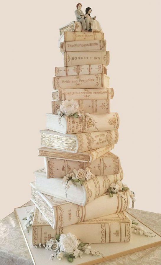 In questa foto una torta perfetta per un matrimonio a tema libri, realizzata con una pila di libri e in cima due sposi intenti a leggere
