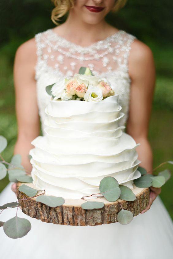 In questa foto una sposa tiene tra le mani una ruffle cake, la torta effetto arricciato. E' poggiata su una base realizzata con il tronco di un albero
