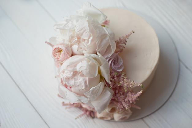In questa foto una torta nuziale rosa, decorata con peonie e astilbe