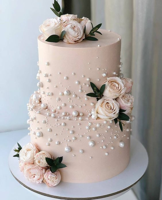 In questa foto una torta nuziale rosa decorata con perle edibili e rose vere