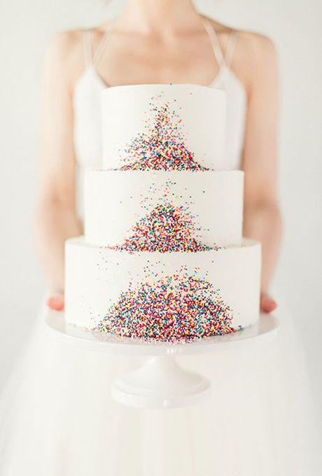 In questa foto una sposa tiene in mano una torta nuziale decorata con confetti colorati