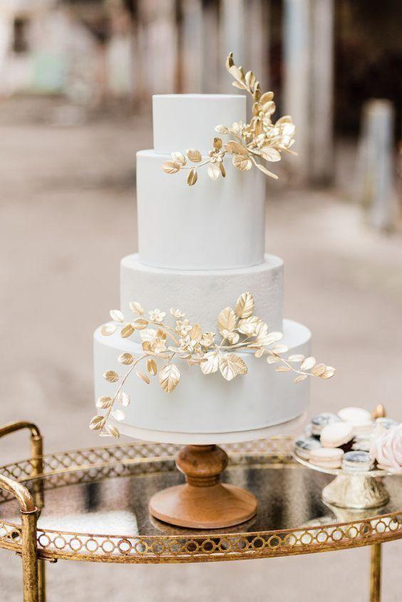 In questa foto una torta di nozze bianca con decorazione 3D nei toni dell'oro