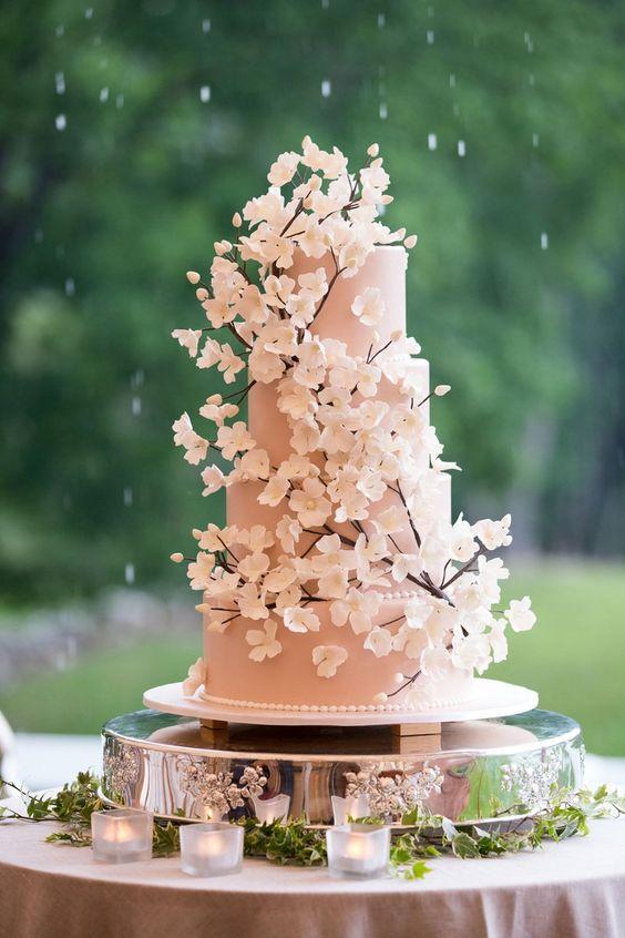 In questa foto una torta per matrimonio a 4 piani rosa con i rami e i fiori di ciliegio come decorazioni 3D