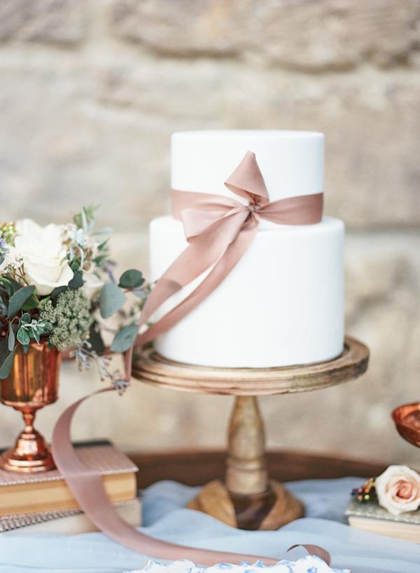In questa foto una torta di matrimonio bianca decorata con un semplice nastro rosa antico