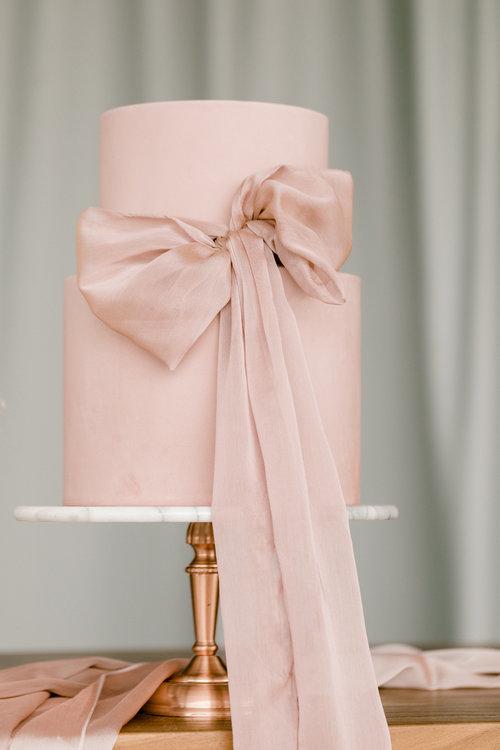 In questa foto una torta di nozze rosa, con un fiocco realizzato con un tessuto della stessa nuance