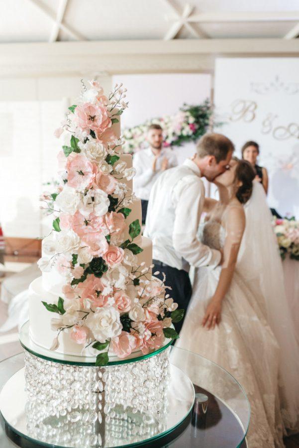 In questa foto una torta per il matrimonio a più piani decorata con fiori freschi e, sullo sfondo, una coppia di sposi intenta a baciarsi