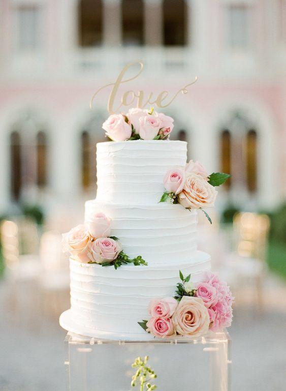 In questa foto una torta matrimoniale floreale: i piani sono decorati con boccioli di rose rosa vere