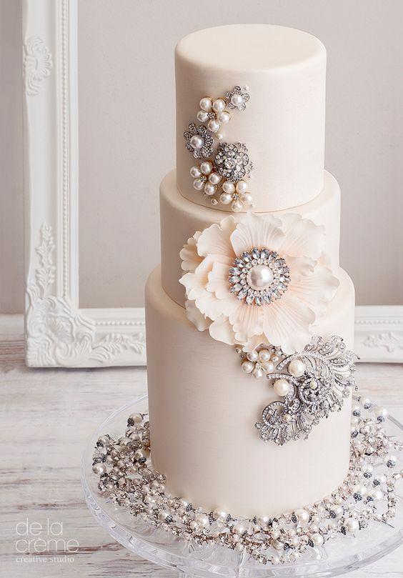 In questa foto una torta decorata con perle e gemme, che rimandano alla mente preziose spille