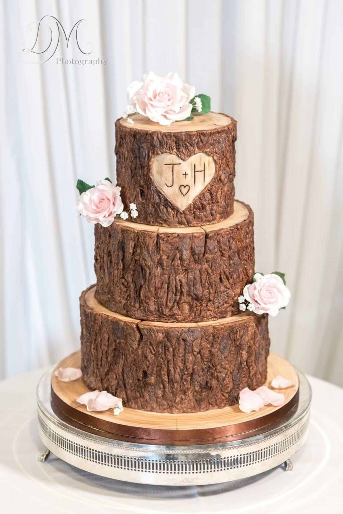 In questa foto una torta matrimoniale che sembra una corteccia d'albero con su inciso un cuore e le iniziali degli sposi