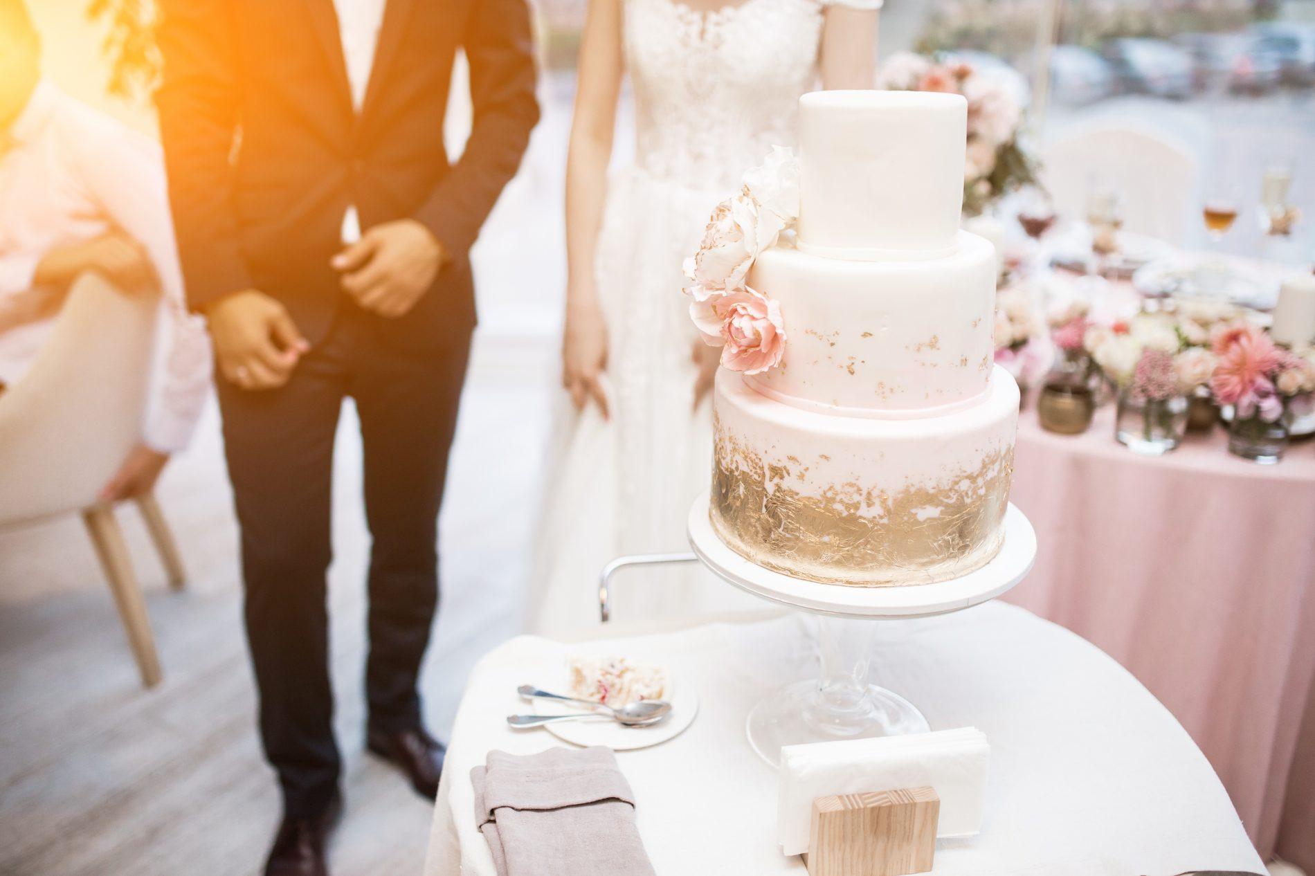 In questa foto una coppia di sposi davanti alla loro torta per matrimonio