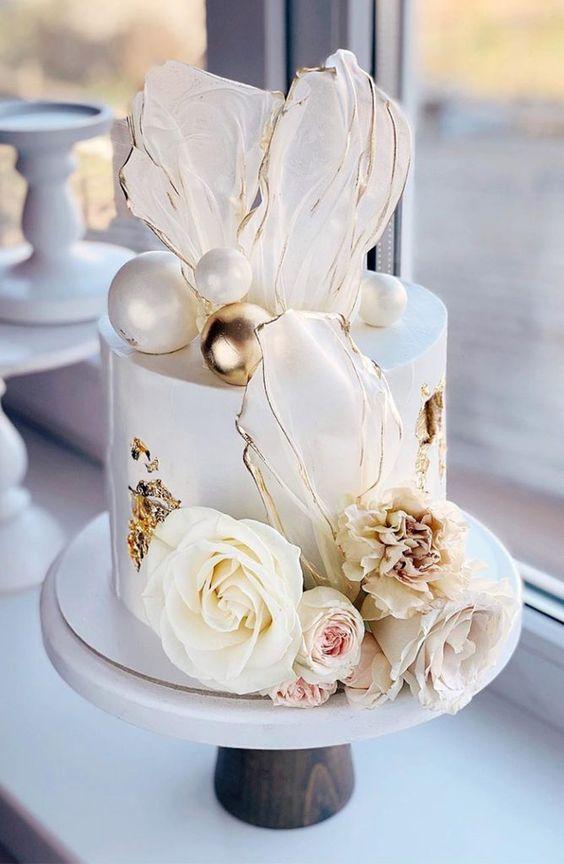 In questa foto una torta di nozze decorata con petali trasparenti e oro realizzati in isomalto