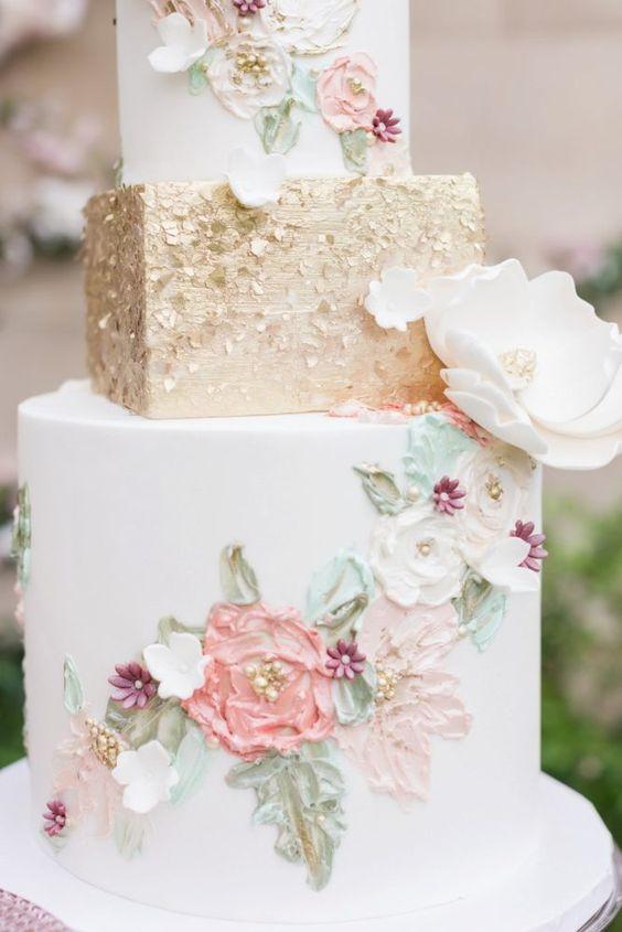 In questa foto una torta a 3 piani, di cui il centrale squadrato, decorata con motivi floreali